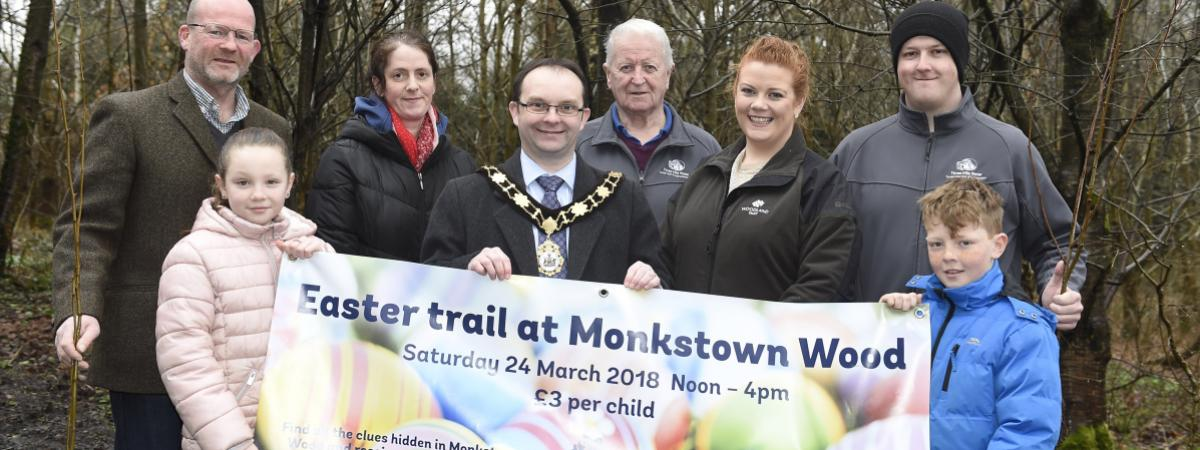 Funders and local people inspect the site improvements at Monkstown Wood.  They are pictured holding up an 'Easter Trail' banner.