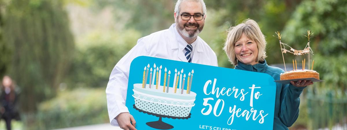 Dr Kienan Savage, senior molecular biologist at QUB, and cancer survivor Emily Stanton encourage everyone to sign up for the Cancer Focus NI Cheers to 50 Years campaign and help raise £100k for locally based cancer research.