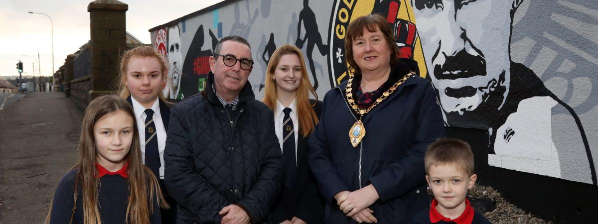 Dave 'Boy' McCauley and Mid and East Antrim Mayor, Cllr Maureen Morrow alongside pupils from Moyle Primary School and Larne High School reveal the new mural.