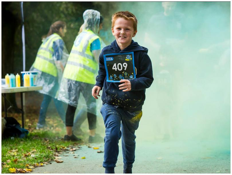 Young boy running through coloured powder