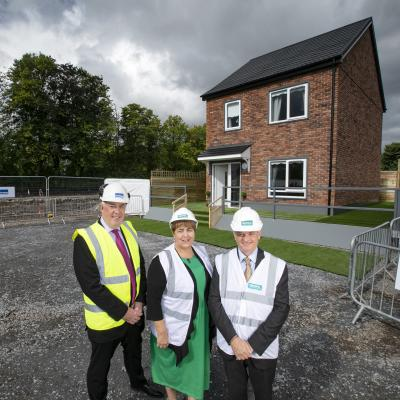 Eugene Lynch, Managing Director of The McAvoy Group, Clare McCarty, Group Chief Executive at Clanmil Housing and David Orr, Chief Executive of the National Housing Federation in front of a prototype house at Clanmil's site in Carrickfergus, where 40 new social homes will be the first in Northern Ireland delivered using off-site construction.
