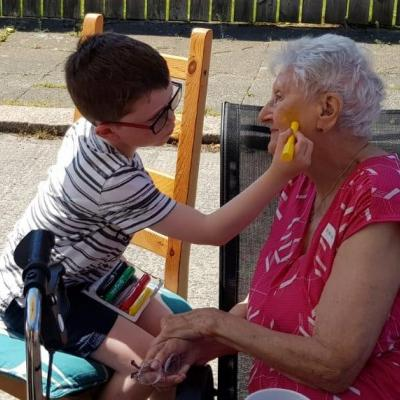 little boy paints older disabled womans face at street party  held as part of The Big Lunch