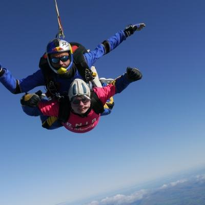 tandem skydivers falling through the blue sky, one wearing a pink RNIB tshirt