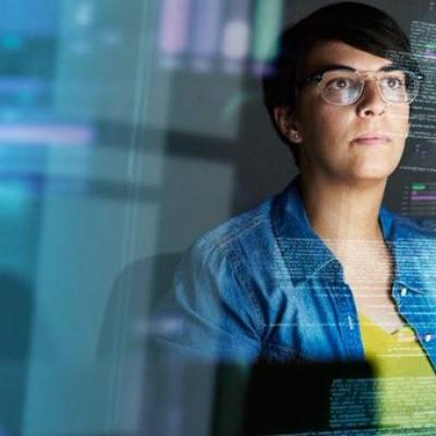 woman looking through a clear screen with data reflected on it