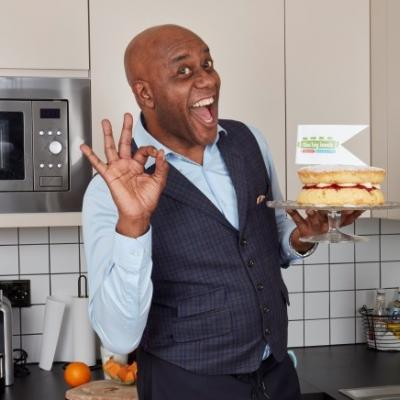 ainsley harriot with big lunch flag and cake looking delighted and holding fingers up  to make ok sign