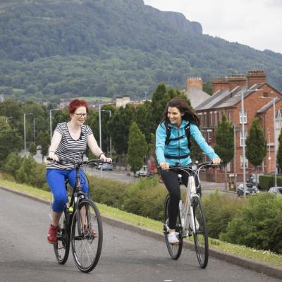 Two women cycling in a park in North Belfast