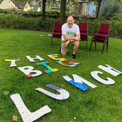 the big lujnch letters on teh grass with a man preparing to invite a few neighbours over for a chat as part of the big Lunch month of community